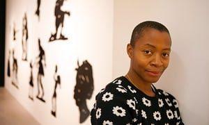 Kara Walker stands in front of her art work